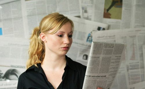 mulher lendo um jornal