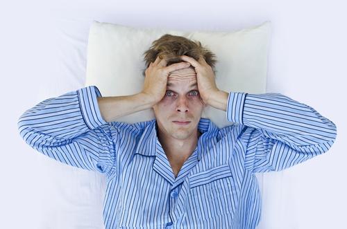 homem deitado em uma cama e preocupado