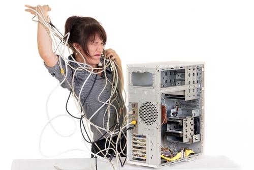 Computador cheio de fios desorganizados.